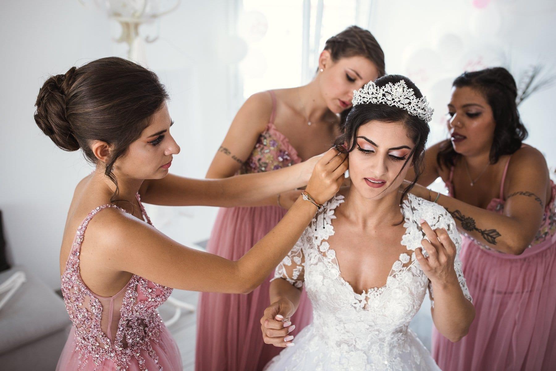 Preparativi sposa aiutata dalle damigelle