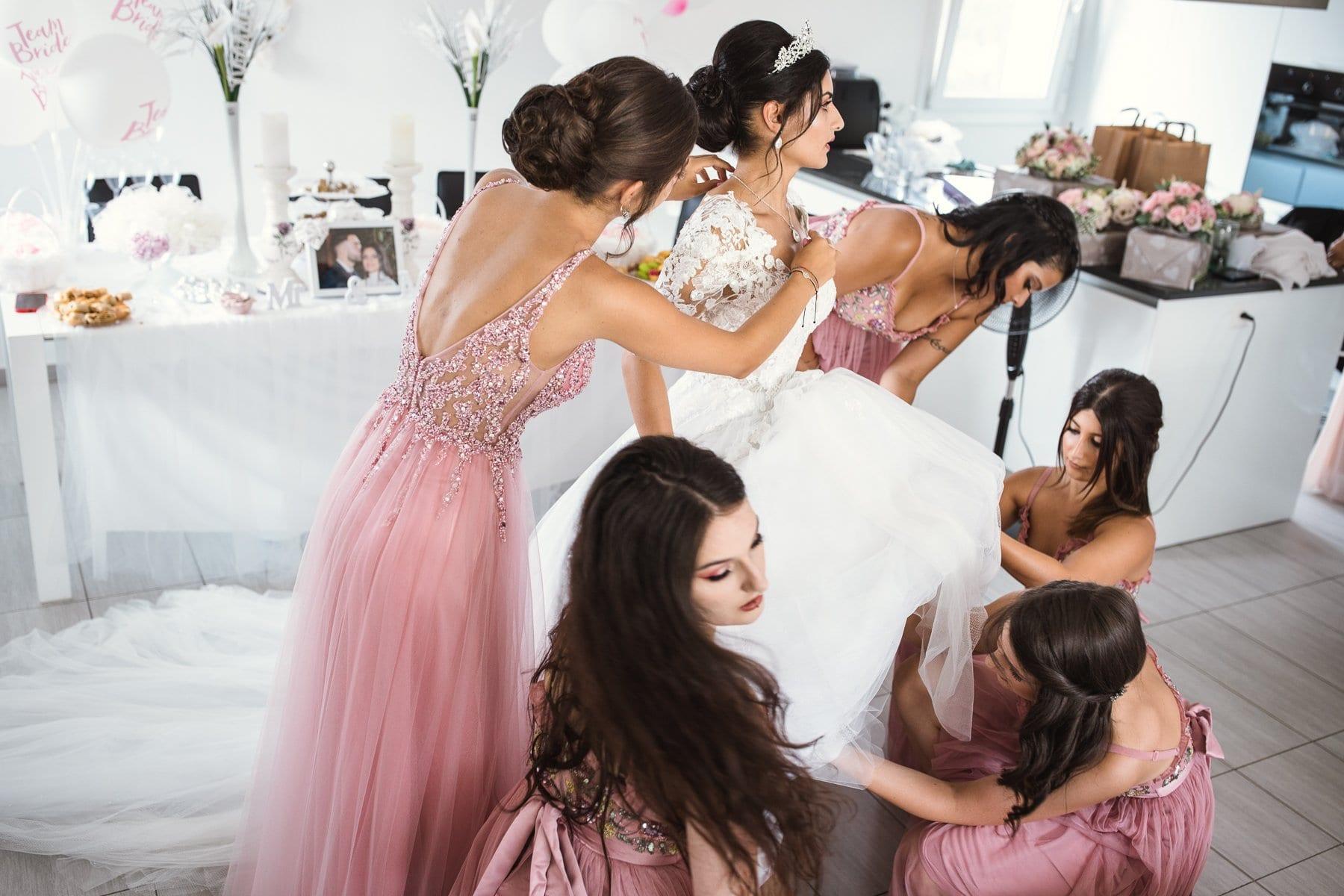 Preparativi sposa aiutata dalle damigelle ad indossare l'abito